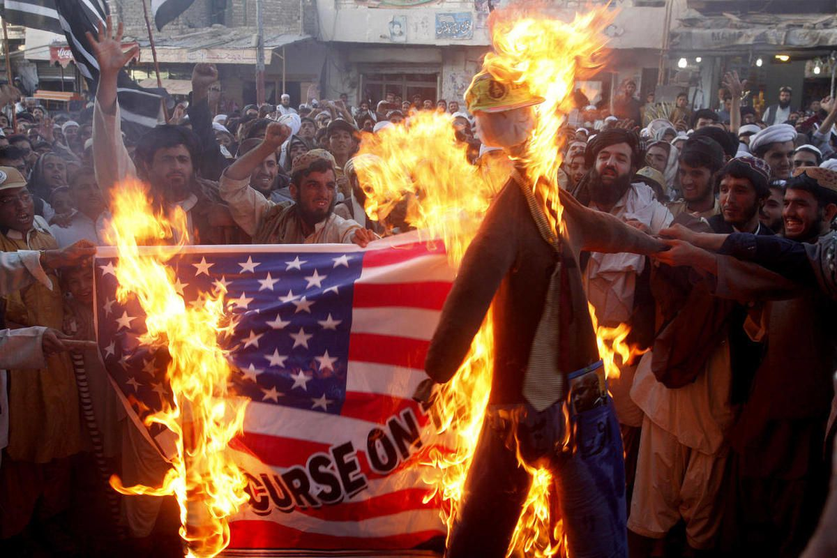 FILE - In this Thursday, Sept. 20, 2012 file photo, Pakistani protesters burn a representation of a U.S. flag and an effigy of U.S. President Barack Obama in the Pakistani border town of Chaman along the Afghanistan border. U.S.-funded ads on Pakistani te