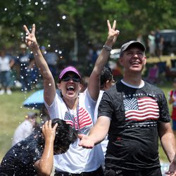 People in the crowd get sprayed with water during the Fourth of July parade in Kaysville on Saturday, July 4, 2015.
