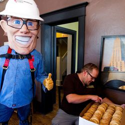 In this June 28, 2013 photo, Rocky Mountain Power mascot Slim the Lineman gives a thumbs up as Craig Christiansen counts out a large order of cookies at his shop, The Chocolate, in Orem, Utah. Christiansen received a message that power was going to be shut off at his business if he did not respond immediately with a payment. Christiansen called Rocky Mountain Power before returning the message. He found out the person who called was a scammer. On Friday, representatives from Rocky Mountain Power decided to purchase 120 snickerdoodles from Christiansen to thank him for helping to spread the word of how to avoid scammers. (AP Photo/Daily Herald, Spenser Heaps)