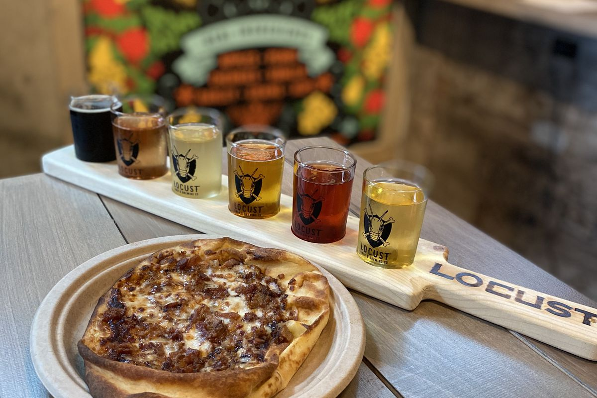 On a wooden table, a small flatbread topped with cheese and meat sits next to a paddle with six small cider glasses.