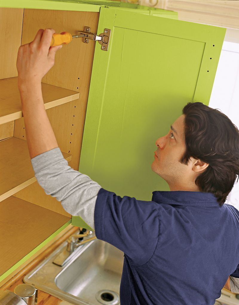 Man Reinstalling Kitchen Cabinets After Painting Them