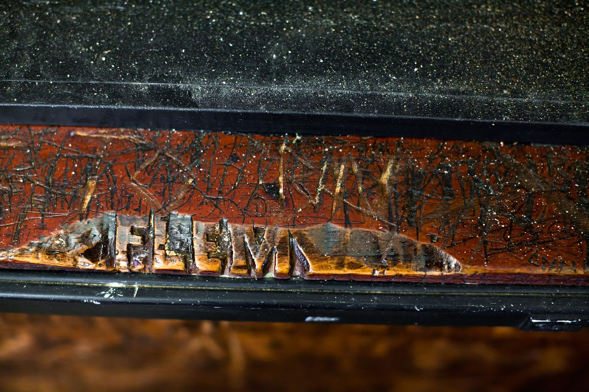 A scratched up old bar rail where someone carved FLEM in block letters