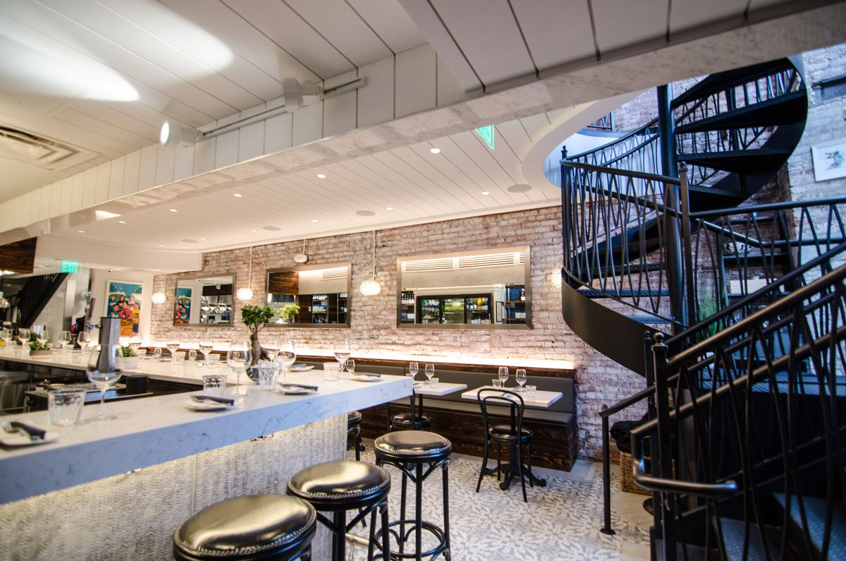 Interior of a restaurant, featuring a black spiral staircase and white marble tables and bar