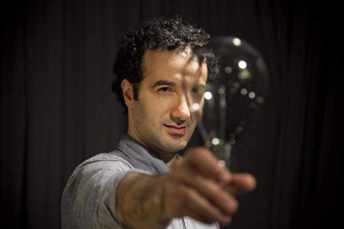 Jad Abumrad, creator of WNYC's Radiolab and More Perfect, looks through a lightbulb