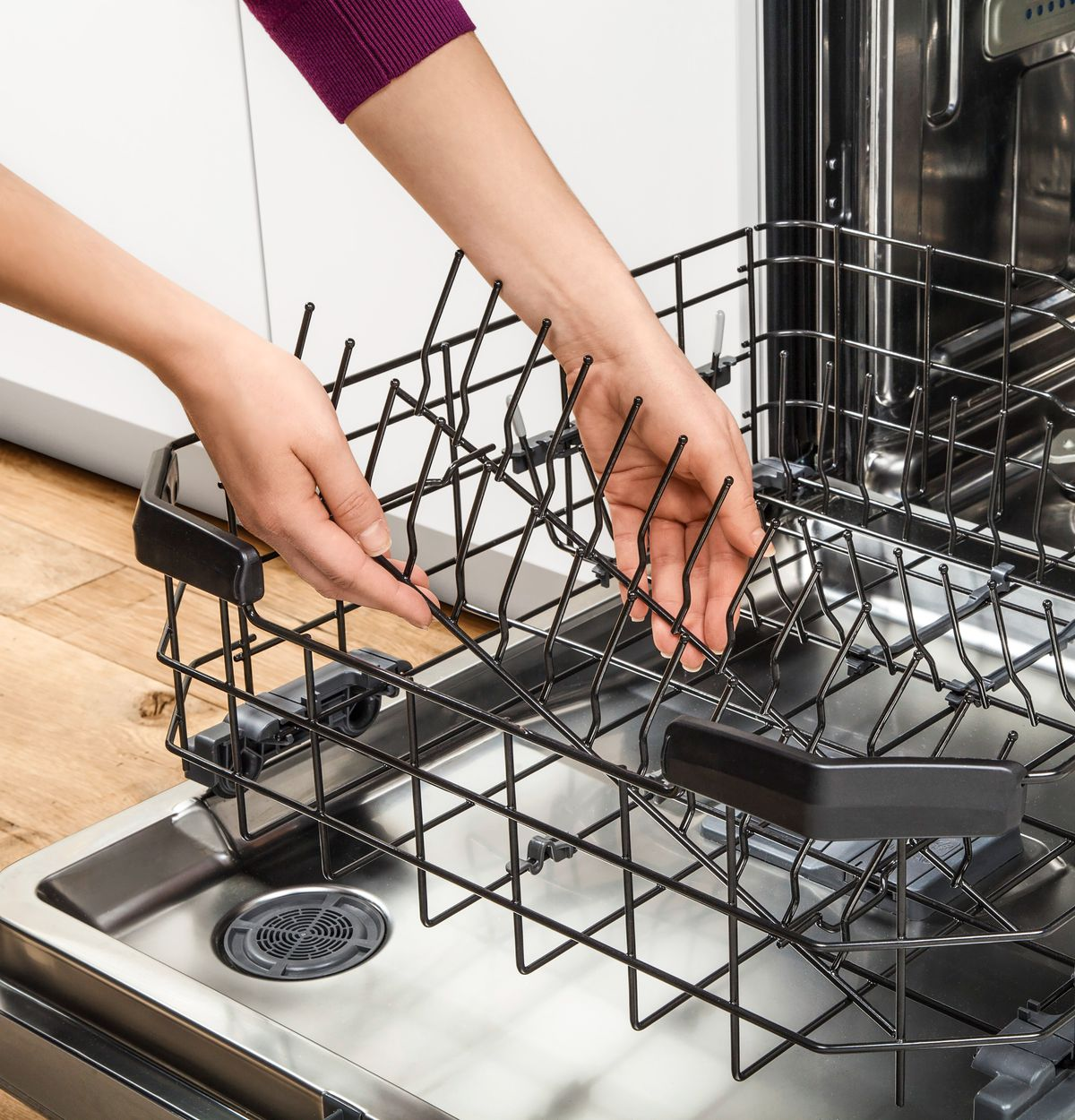 Person cleaning dishwater rack.