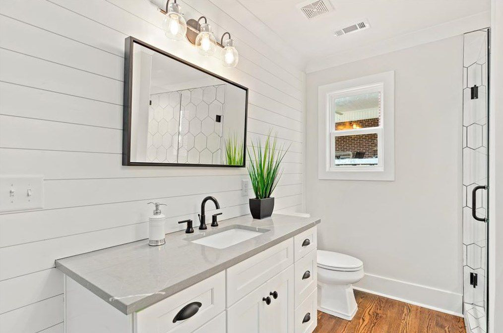 A white bathroom with shiplap on a wall.