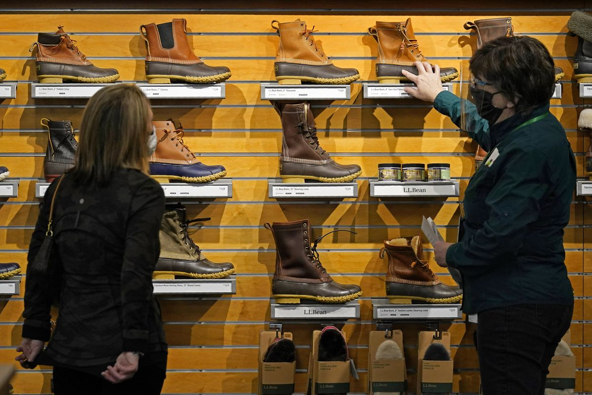 In this March 18, 2021 file photo, a salesperson helps a customer shopping for Bean Boots at the L.L. Bean flagship retail store in Freeport, Maine.