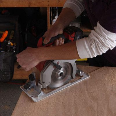 Person using a circular saw to cut the edges of the poker table.