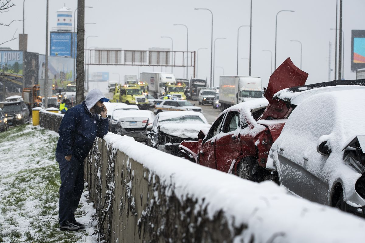 A man talks on his phone on the shoulder of the Kennedy Expressway after a massive pileup crash involving nearly 60 vehicles sent more than a dozen people to hospitals in the inbound lanes of the expressway near North Avenue, Wednesday morning, April 15, 2020.