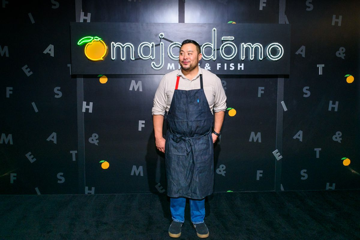 A chef stands in front of a sign