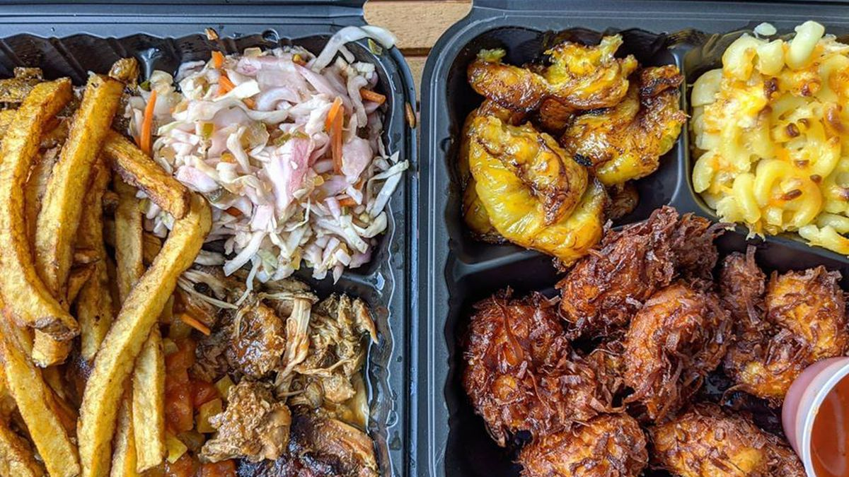 Overhead view of two black takeout containers on a picnic table. One contains jerk chicken with sides of fries and a slaw, while the other contains fried, coconut-encrusted shrimp with mac and cheese, plantains, and a small plastic cup of dipping sauce.