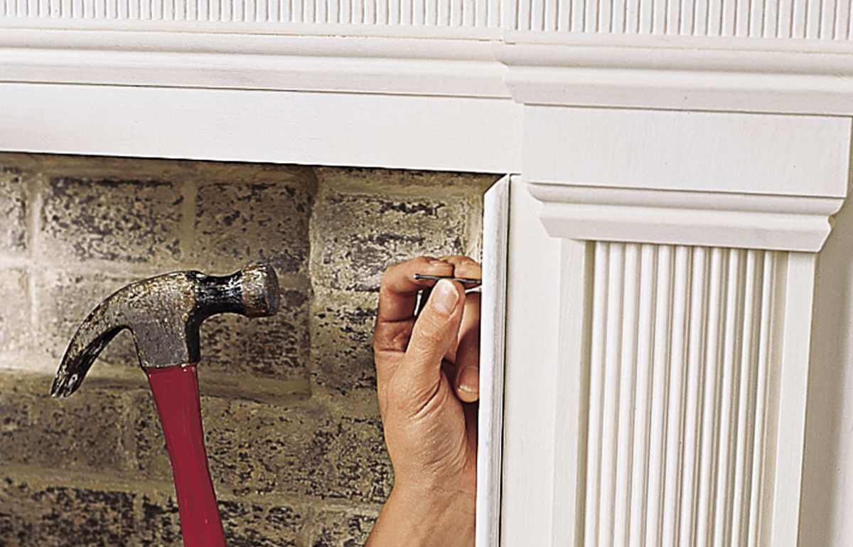 Man Hammers In Finish Nails Along Edge Of Mantel
