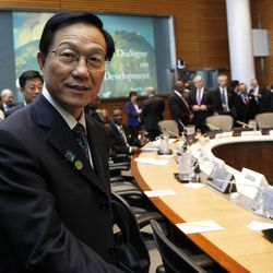 China's Finance Minister Xie Xuren walks to his seat during a meeting on sustainable development at the IMF and World Bank Group Spring Meetings in Washington, Friday, April 20, 2012.
