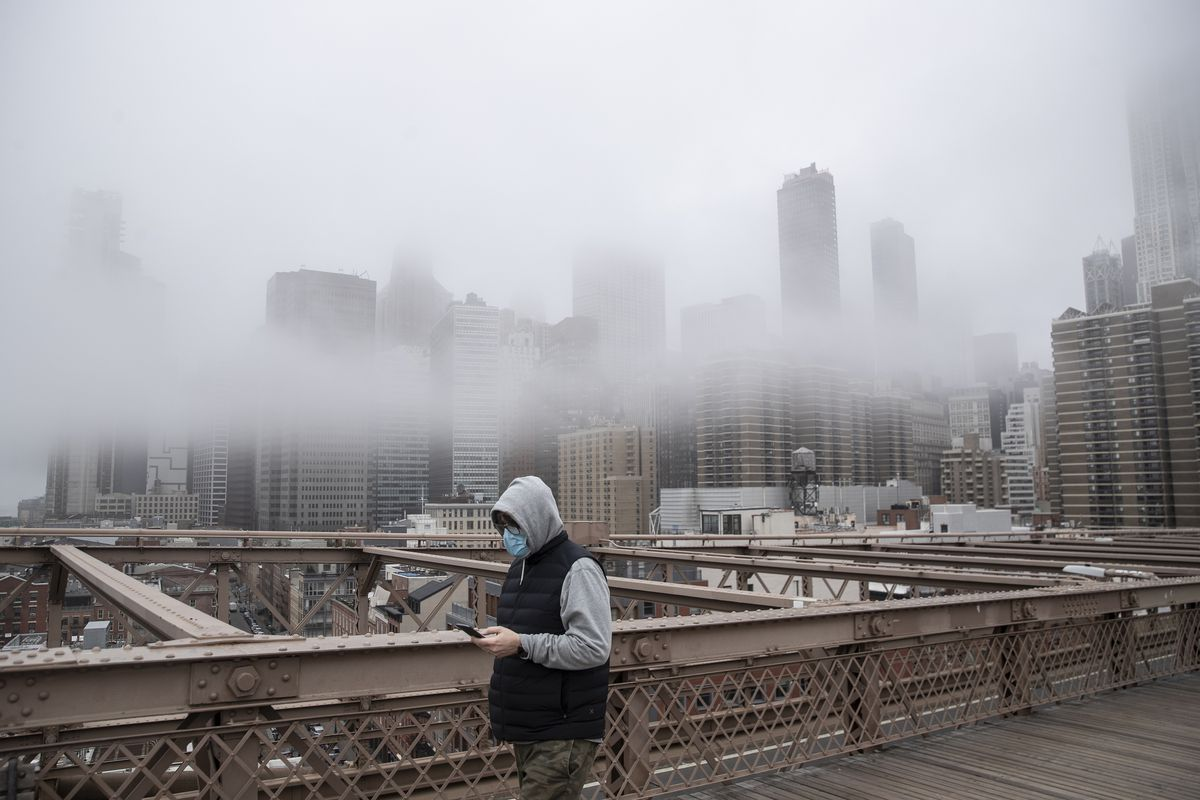 With mist shrouding the skyscrapers behind him, a man in a blue face mask and a grey hoodie walks across the bridge, looking down at his phone.