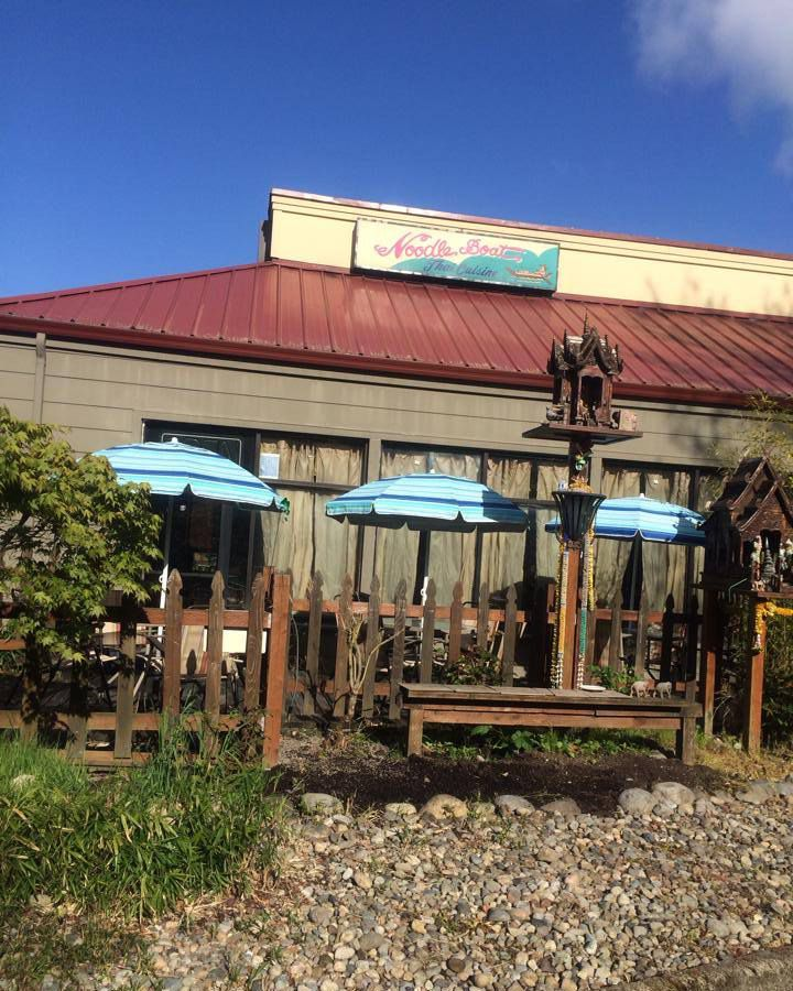 The exterior of Noodle Boat Thai Restaurant, with a patio and light blue umbrellas.