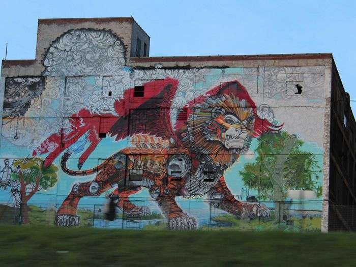 A building with a mural on it. The mural depicts a chimera.
