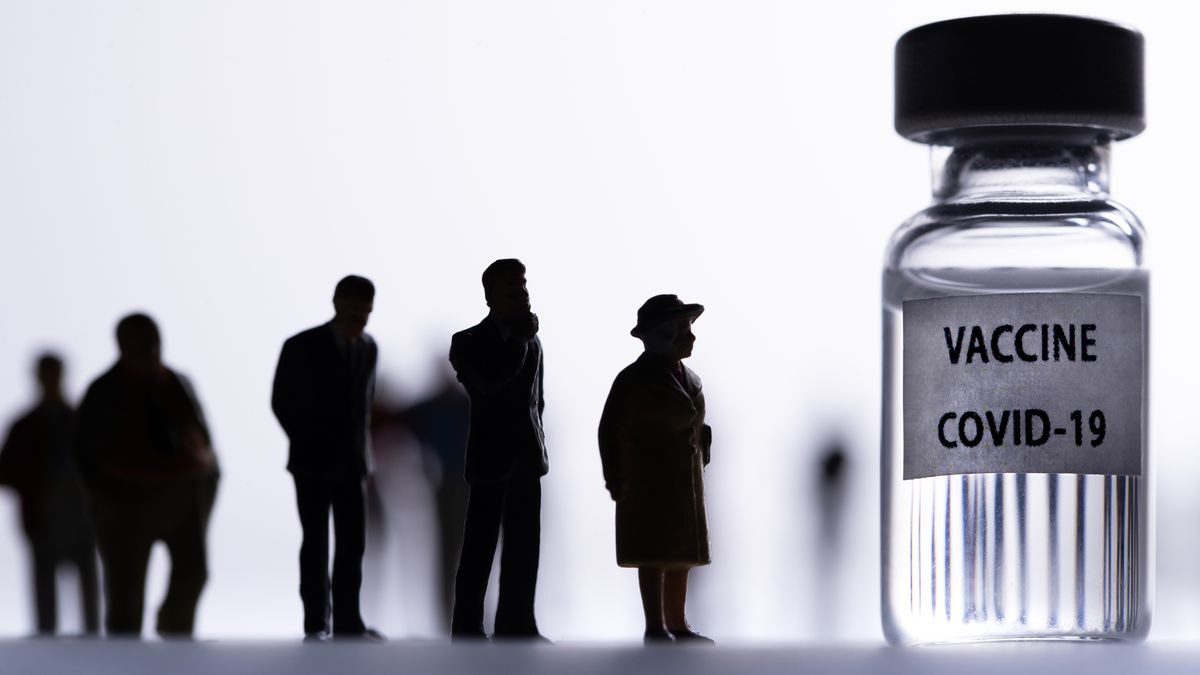 """Silhouetted people lining up in front of a medical vial labeled """"vaccine Covid-19."""""""