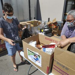 Salt Lake City Mission volunteers Rose Eyre, left, and Raymette Francom pack boxes with food during the mission's Father's Day FoodBox Giveaway in Salt Lake City on Friday, June 19, 2020. The mission is providing the vital relief to families suffering financial loss due to the COVID-19 crises. The volunteers loaded food boxes into cars as they drove up to the mission's Salt Lake location at 1151 South Redwood Road.