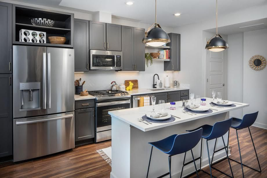A white kitchen with blue chairs.