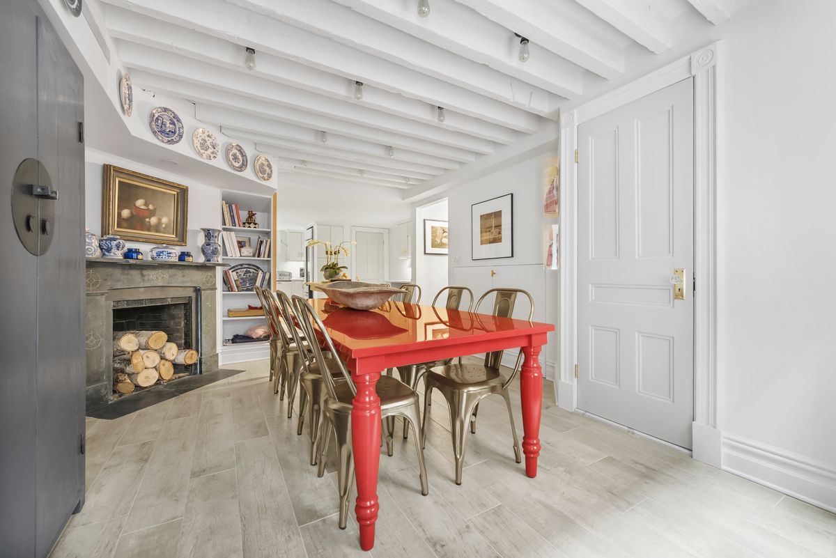 A dining area with wood beams, white walls, a fireplace, and a red dining table.