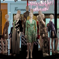 In the center is a three tiered podium containing thirteen mannequins decked out in vintage recreations of Diane's original and most famous prints— green and white palms, python, leopard, chain links, geometric cubes and Diane's own signature. But t