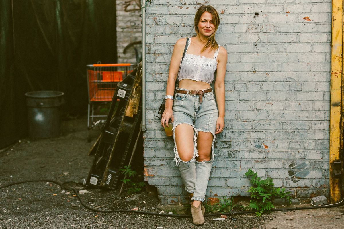 A woman in a white crop top and jeans with holes against a brick wall.