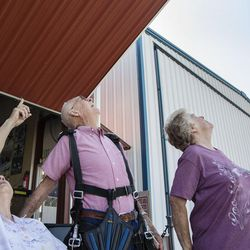 Mary Ashcroft, left, her husband, Wendell, and their daughter, Nancy Harris, look up to the sky to watch their first two family members parachute to safety at Skydive Ogden in Ogden on Saturday, Aug. 5, 2017. There were eight family members that went skydiving and they went in separate groups of two and three.
