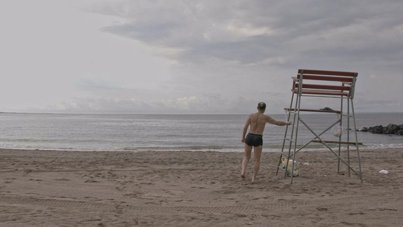 A New Yorker watching the sea from the beach in The Hottest August.