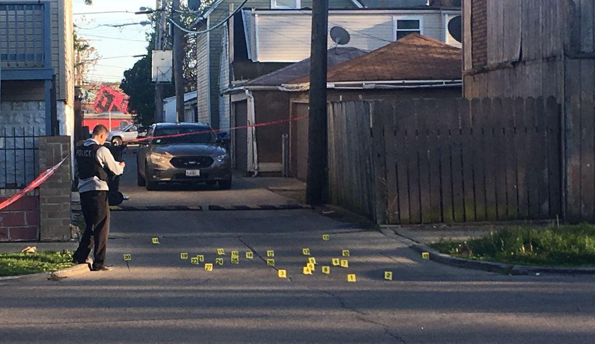 A Chicago Police officer at the scene with 27 yellow evidence tags. That's where the two shooters opened fire, police said. | Lauren Fitzpatrick/Sun-Times