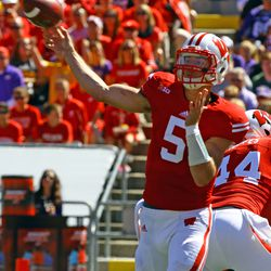 Tanner McEvoy throws a pass in the first half