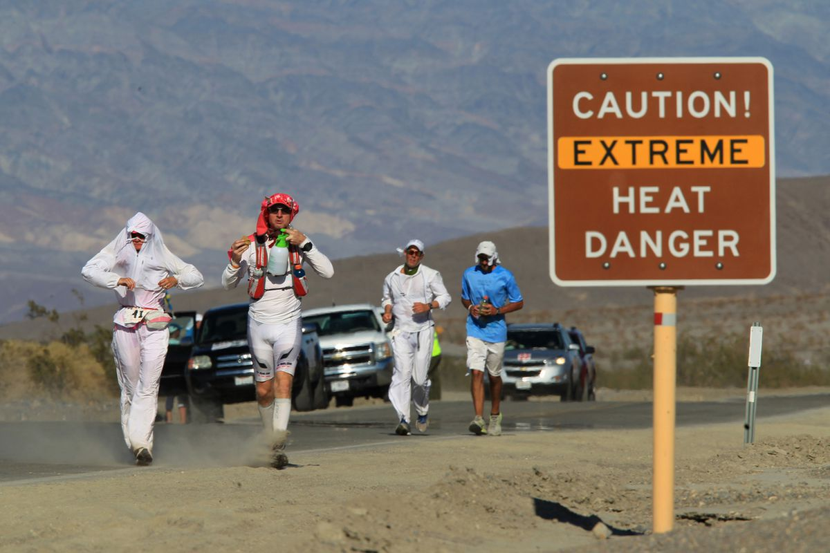Runners pass a heat danger warning sign during the AdventurCORPS Badwater 135