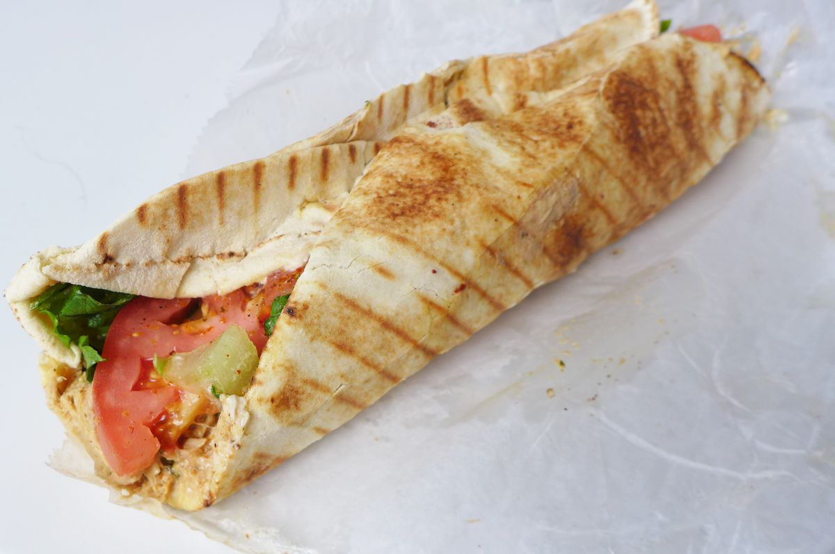 A tubular wrap made with a grilled flatbread, a tomato slice peeking out the end.