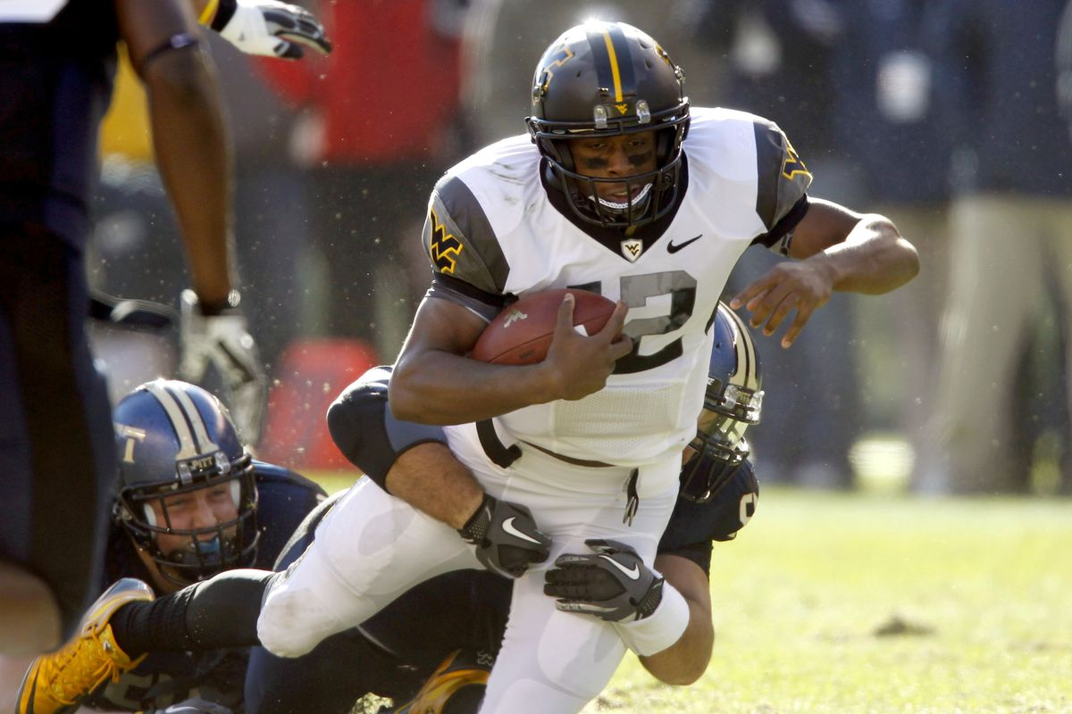 West Virginia running back Shawne Alston (20) is tackled from behind during an NCAA football game