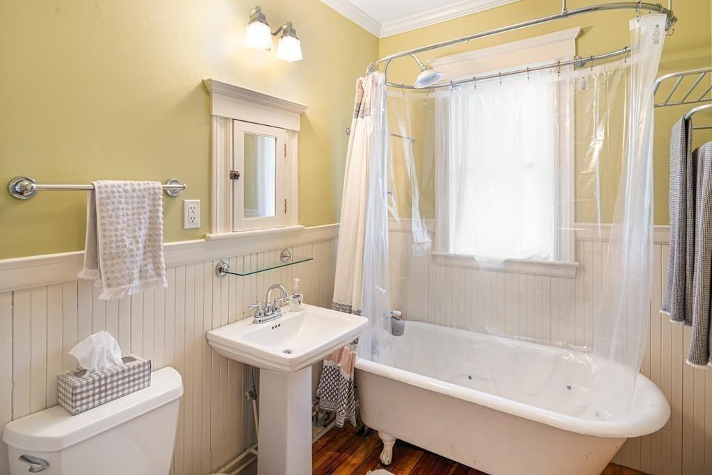 A bathroom with a clear shower curtain around the tub.