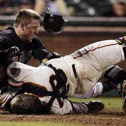 FILE - This May 25, 2011 file photo shows Florida Marlins' Scott Cousins, top, colliding with San Francisco Giants catcher Buster Posey (28) on a fly ball from Emilio Bonifacio during the 12th inning of a baseball game in San Francisco. Posey knows the day will come when he again has to step toward the third-base line, watch a charging runner trying to score and brace himself for a collision.