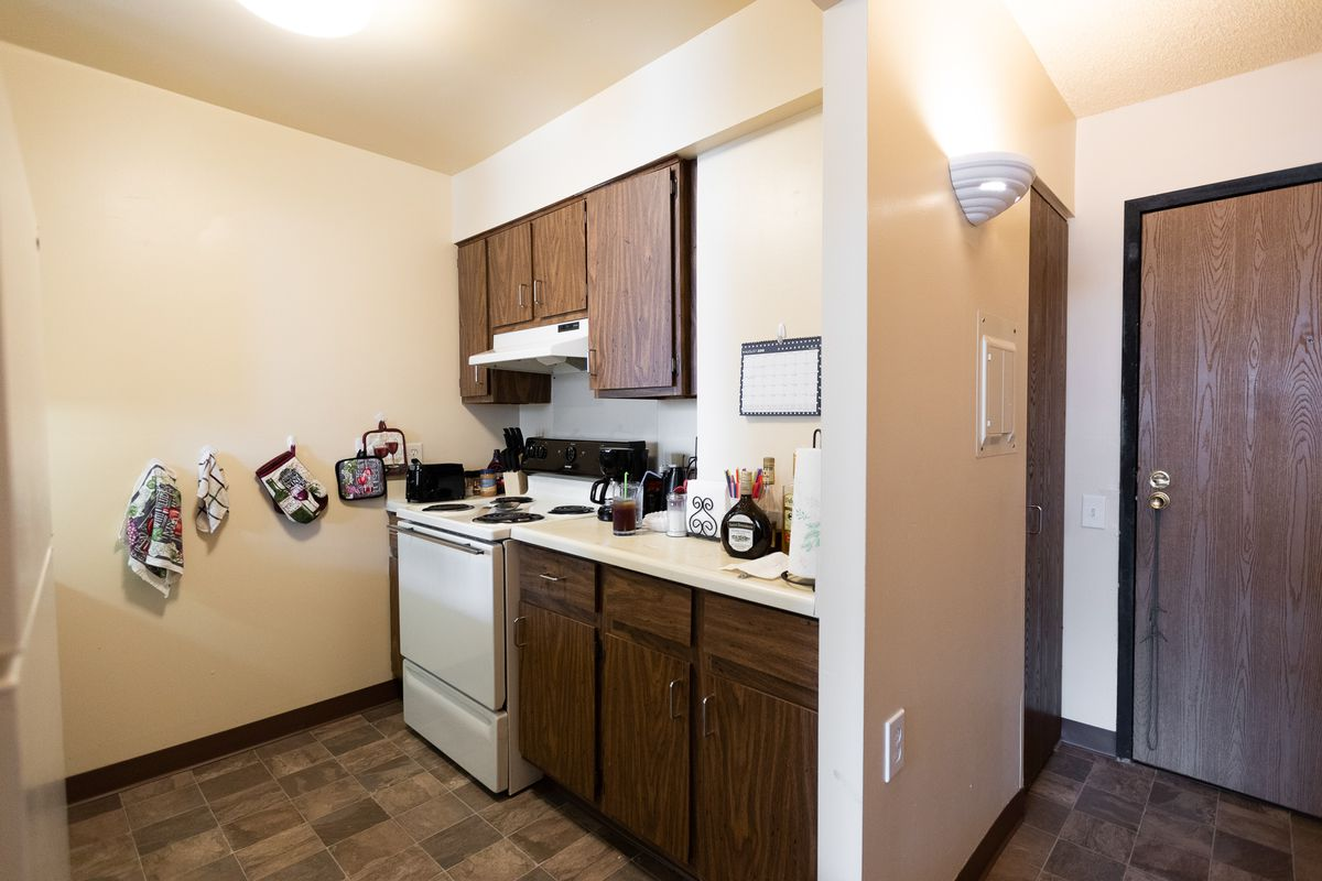 A tiny kitchen with black cabinets, electric range stove, and oven mitts and tea towels on hooks. Nearby, there's light switch that's level with the front door knob.