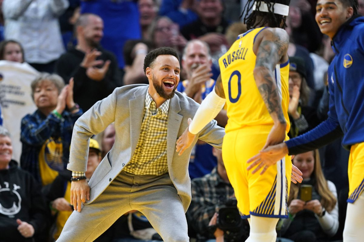 Golden State Warriors guard Stephen Curry congratulates guard D'Angelo Russell during the fourth quarter against the Orlando Magic at Chase Center.