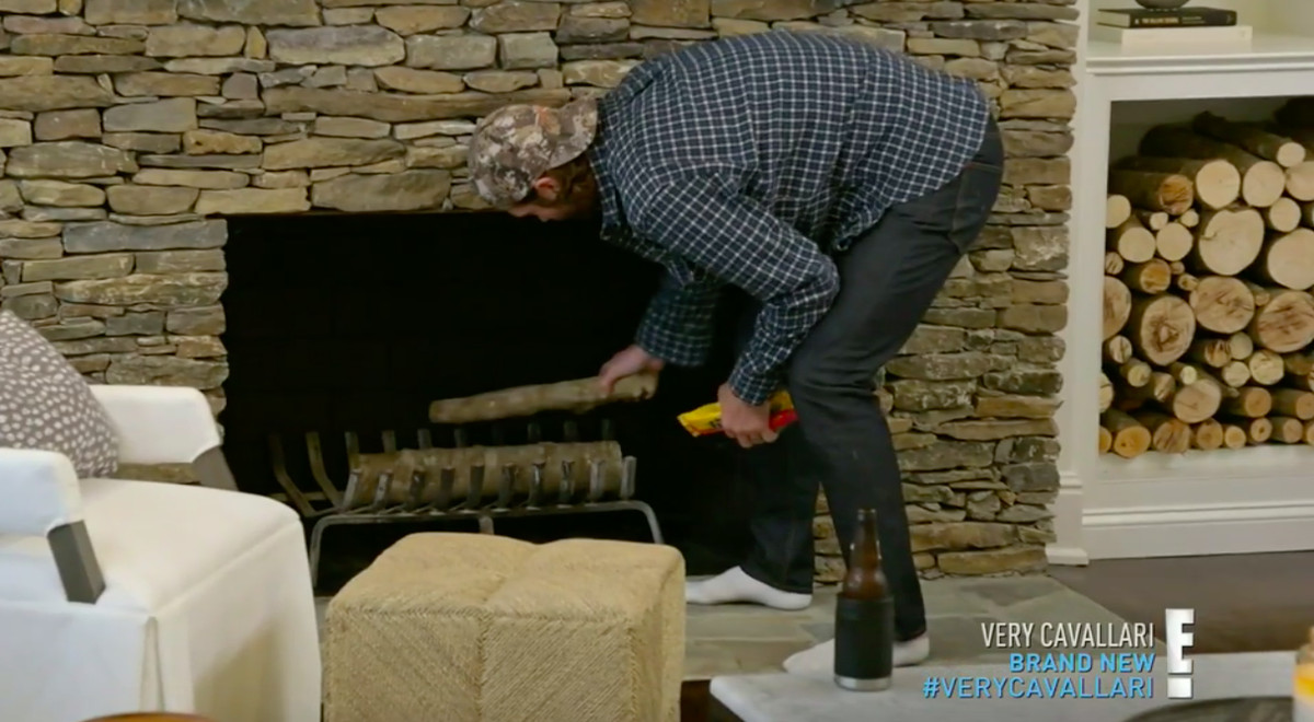 Jay Cutler putting two logs into a fireplace