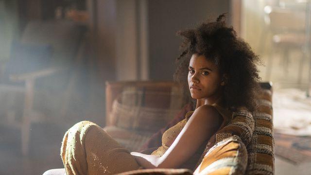 Zazie Beetz sits on a striped couch in dim light in Nine Days