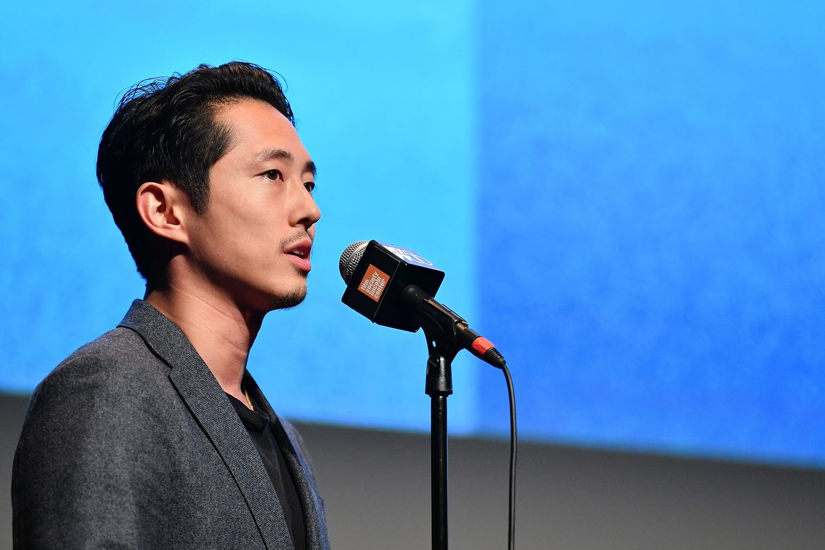 Steven Yeun speaking into a microphone