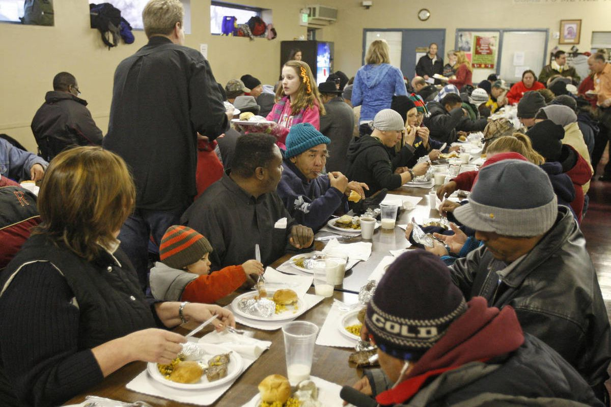 Volunteers serve steak dinners and all the trimmings with gifts for all guests for homeless and low-income individuals and families at St. Vincent de Paul Soup Kitchen.