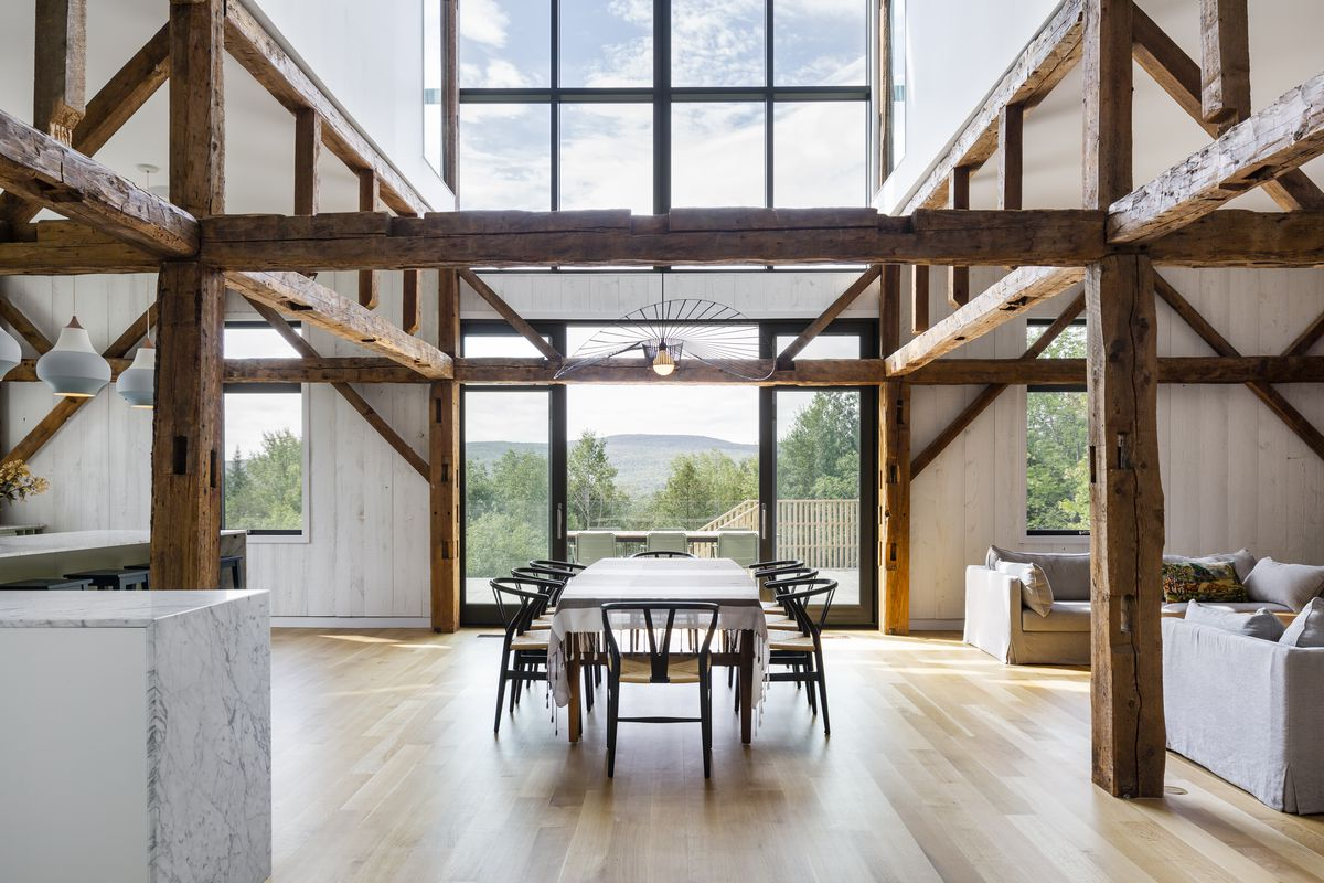 Open plan dining room with 30 foot ceilings made from the restored barn wood. A dining room table sits in the center.