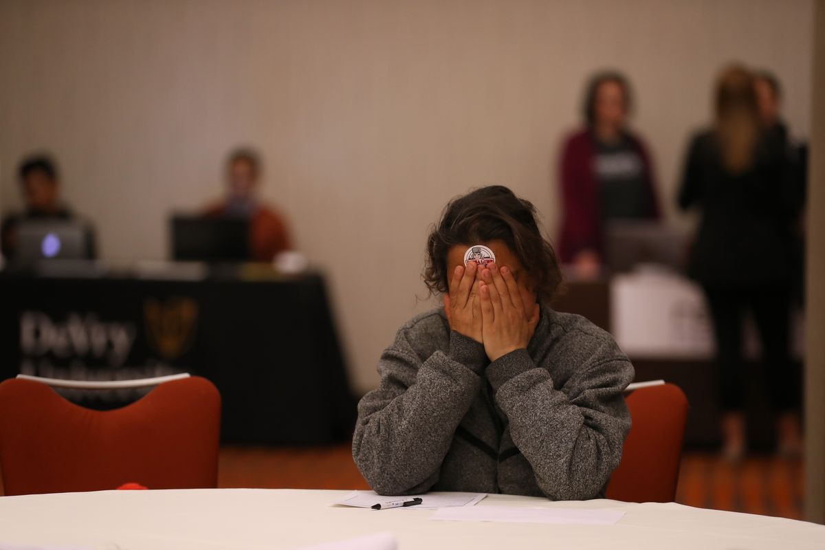 A woman seated at a table puts her hands over her face head while filling out a job application at a career fair.