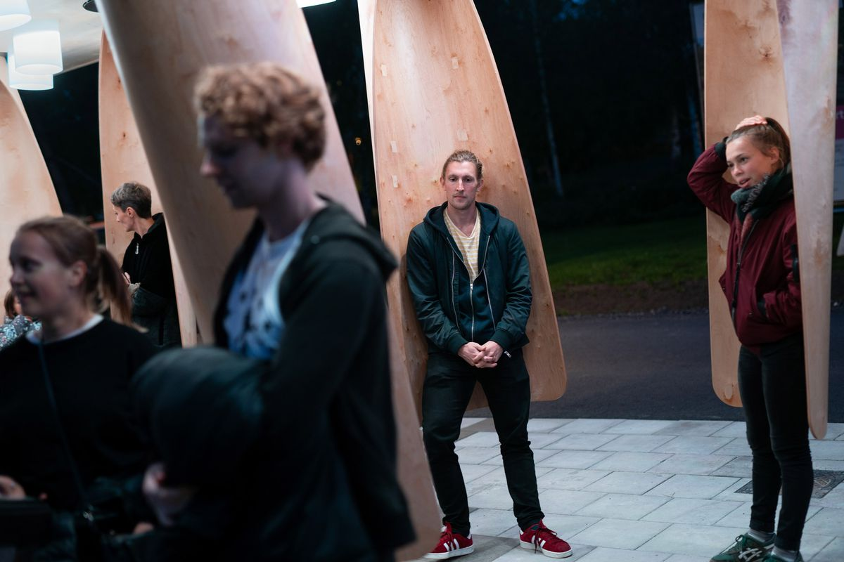 People standing in timber pods at bus stop.