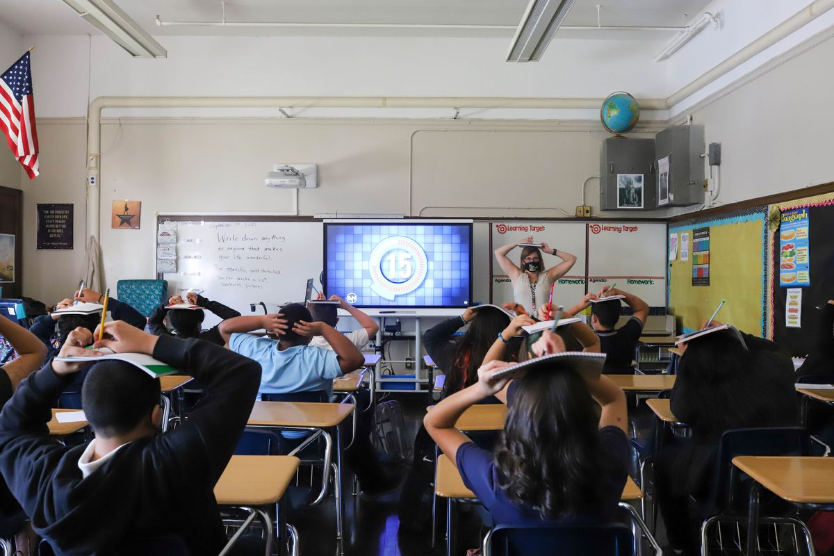 Students and their teacher balance their notebooks on their heads during class on the first day of school.