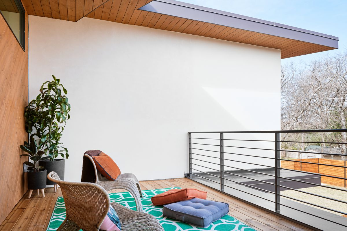 Photo of a balcony with a wood deck and roof overhang. There's a wood wall in back and stucco wall on the side. Two wicker chairs are arrnged on a rug with floor pillows facing a metal railing. There are tall potted plants in the corner.