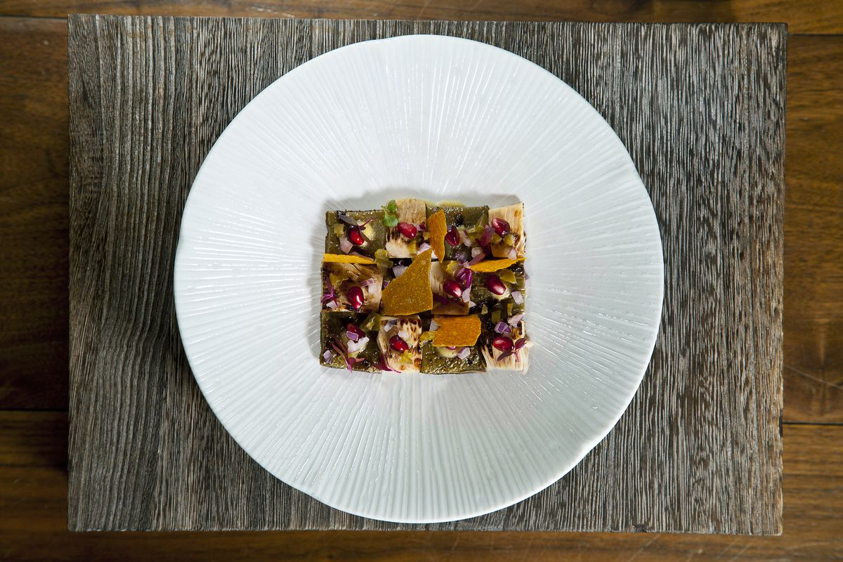 An overhead photograph of a dish that appears to be composed of dried fruits, nuts, cactus, jackfruit, and pomegranate seeds