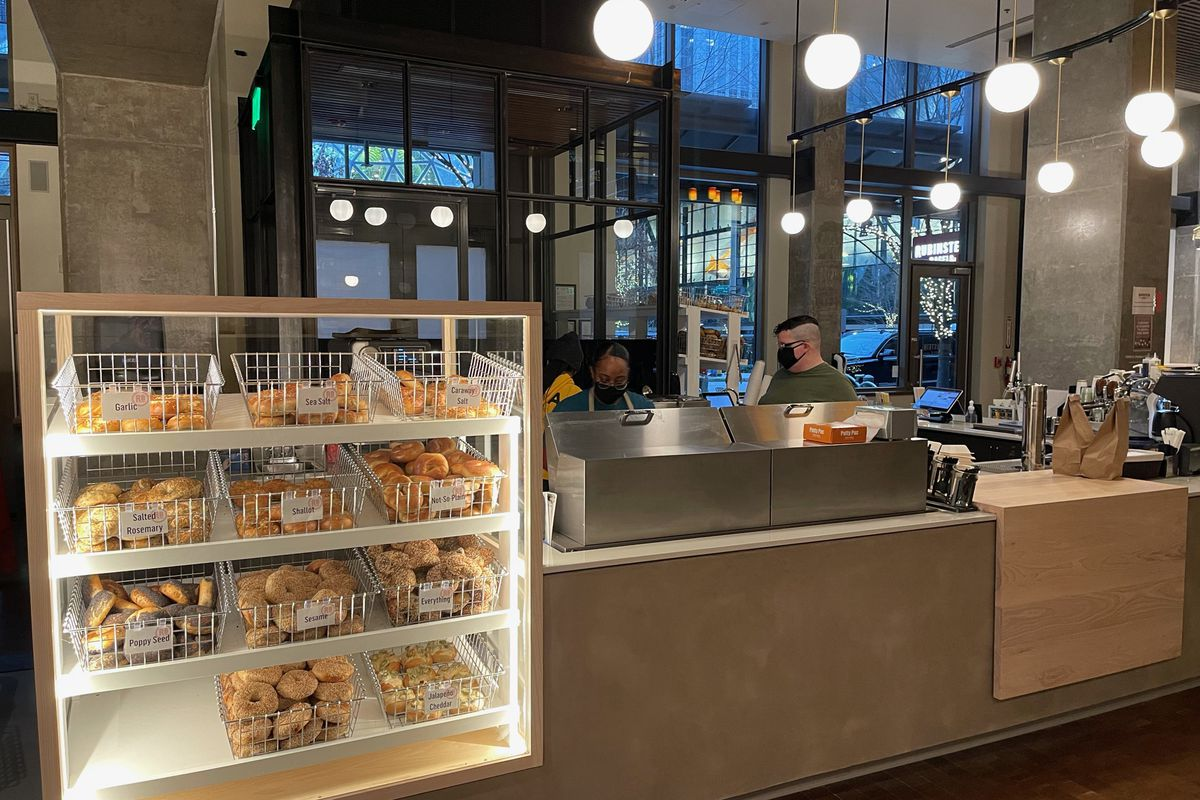 A view of a small cafe with a display case showing baskets of bagels and two masked workers behind the counter