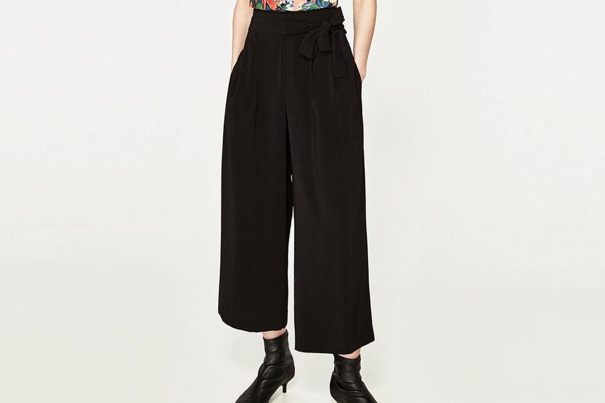 A model wearing black culottes and a floral blouse