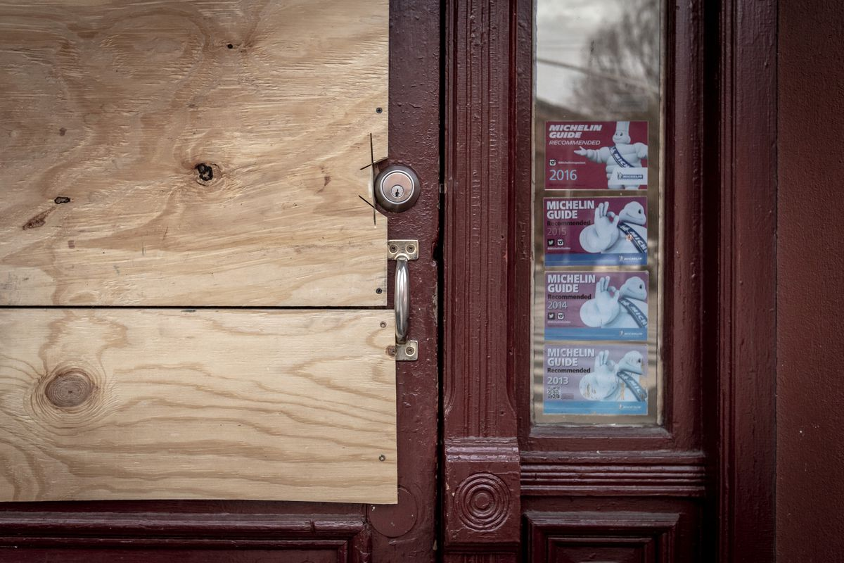 The front of a restaurant door is covered in plywood, with a small cut-out area for the lock and door handle